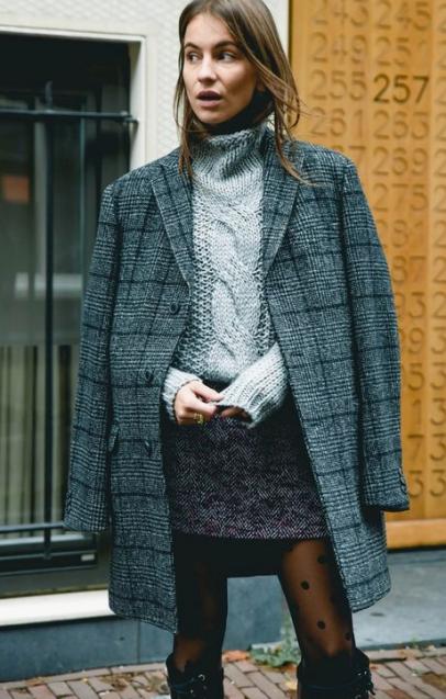 Avec un pardessus d'homme, un gros pull et une mini en tweed